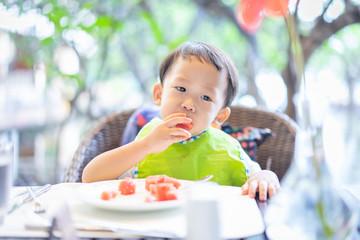 A boy is eating watermelon in the breakfast.