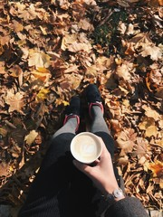 Photo of female legs against a background of yellow leaves with coffee. Vertical shot.
