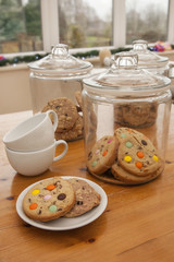 Cookies in glass jars, with coffee cups in a cafe/restaurant
