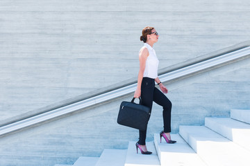 business woman with laptop on stairs