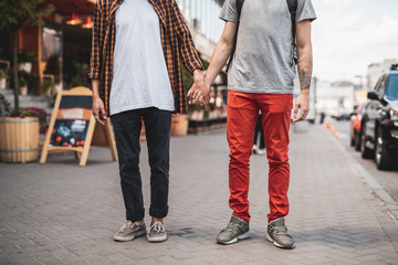 Man holding hand of friend while standing on sidewalk on street. Comrades spending time together concept