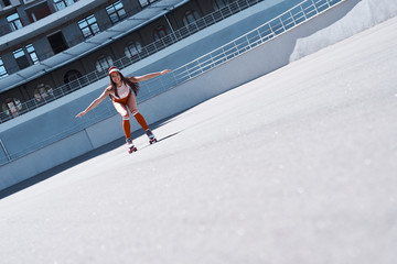 Beautiful girl is riding in rollers in skate park. She is doing that very active. She is happy.