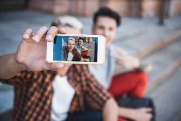 Portrait of happy guys taking photo on phone outdoor. They demonstrating screen of gadget for camera while keeping it in arm