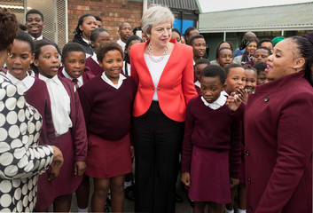 Britain's Prime Minister Theresa May poses for a picture with school children during a visit to the ID Mkhize Secondary School in Gugulethu near Cape Town