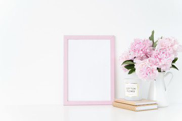 Cute pink portrait a4 frame mock up with a pink peonies in jug beside the frame, overlay your quote, promotion, headline, or design, great for small businesses, lifestyle