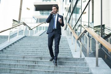 Successful businessman holding smartphone