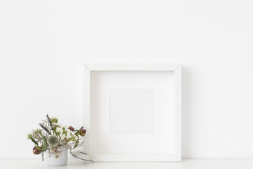 Stylish white square portrait frame mockup with small bouquet of dried flowers in small white pot on white wall background. Empty frame, poster mock up for presentation design.