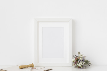 Cute white a5 portrait frame mockup with bouquet of dried flowers, gold stamp and printing on white wall background. Empty frame, poster mock up for presentation design.