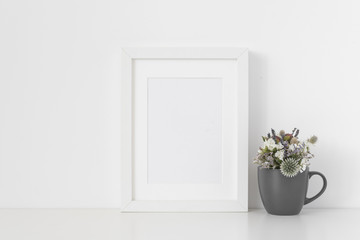 White A5 portrait frame mockup with small bouquet of dried flowers in gray mug on white wall background. Empty frame, poster mock up for presentation design.