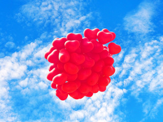 Scarlet heart shaped balloons against the blue sky. Soft focus processing. Symbols of love, romance and day of Saint Valentines , conceptual background. Red balls in the shape of heart