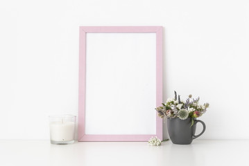 Pink portrait frame mockup with dried field wild flowers in gray mug . Background