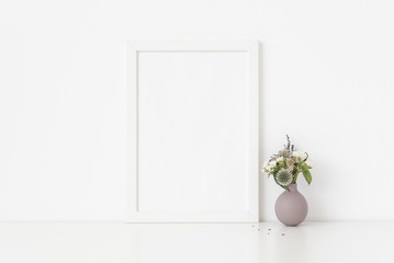 Minimal white a4 portrait frame mockup with dried field wild flowers in vase on white wall background. Empty frame, poster mock up for presentation design.