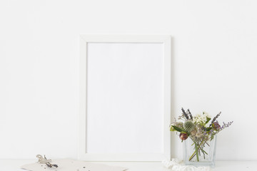 Modern white a4 portrait frame mockup with bouquet of dried flowers in transparent vase and clamp on white wall background. Empty frame, up for presentation design.