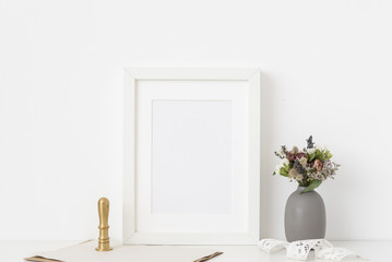 White a5 portrait frame mockup with dried field wild flowers in vase and gold stamp on white wall background.  Template frame for text, lettering, modern art.