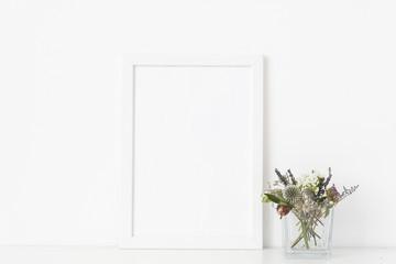 Minimal white a4 portrait frame mockup with dried field wild flowers in transparent vase on white wall background. Empty frame, poster mock up for presentation design.