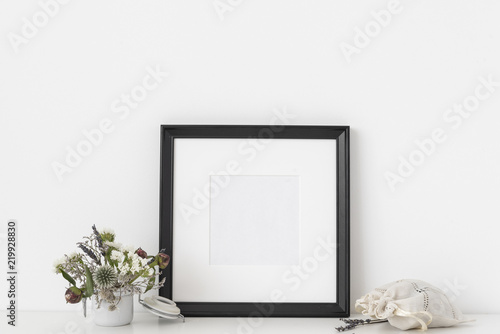 77250a7af604 Black square portrait frame mockup with dried field wild flowers in pot and  sachet with lavender on white wall background. Empty frame