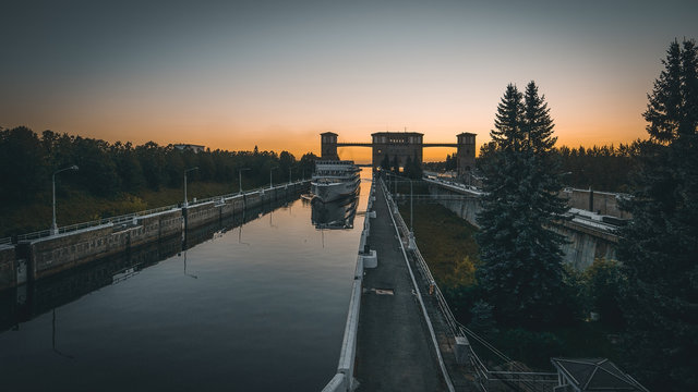 Cruise ship enters gates of shipping locks at sunset, water transportation concept