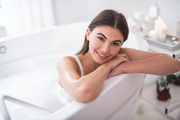 Portrait of happy lady with attractive smile looking at camera while leaning on side of white bath during cosmetic procedure in spa salon