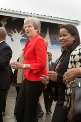 Britain's Prime Minister Theresa May joins school children in dancing during a visit to the ID Mkhize Secondary School in Gugulethu near Cape Town