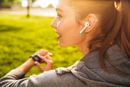 Portrait of beautiful sporty woman 20s in sportswear using smartwatch and wireless earbud, while resting in green park