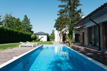 view of house, garden and swimming pool with sunbeds for relax