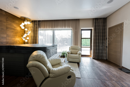Interior of empty modern room with armchairs and closed jacuzzi in