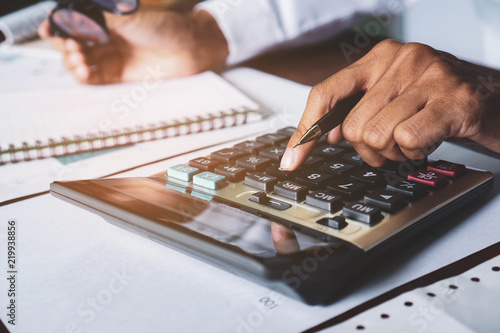 businessman is using calculators to calculate and analyze the