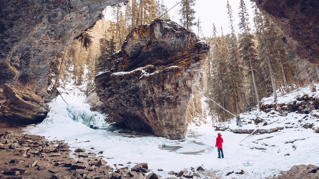 Person in snowy woods with big rocks