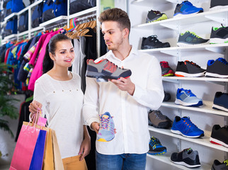 loving couple deciding on new sneakers in sports store