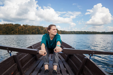 Young beautiful woman tourist traveler rowing oars on a wooden boat on the lake on a sunny day