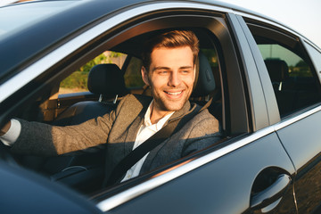 Front view of smiling bussinesman in suit driving Wall mural