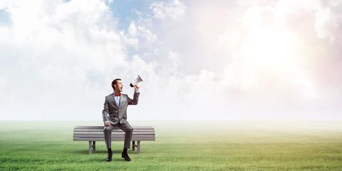 Businessman in summer park announcing something in loudspeaker