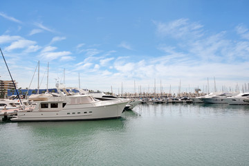 Beautiful port of Alicante, Spain at Mediterranean sea. Luxury yachts, ships, ferries and fishing boats sailing and standing in rows in harbor. Rich people traveling around the world. Sunny evening