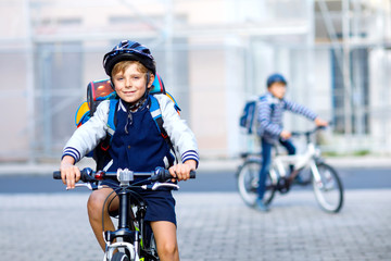 Two school kid boys in safety helmet riding with bike in the city with backpacks. Happy children in...
