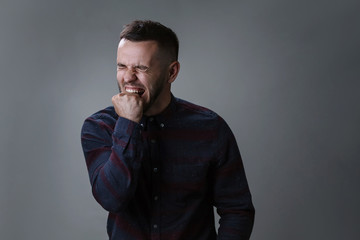 Portrait of angry and depressed man biting his fist desperate feeling frustrated and helpless in depression and sadness facial expression concept on dark gray background