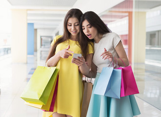 Surprised women with smartphone and shopping bags