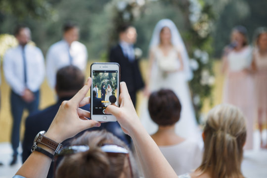 guest at the wedding ceremony takes pictures on the phone of the newlyweds