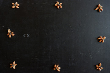 Black wooden background with a pattern. Seeds in the form of a flower on the board. Free space for design.