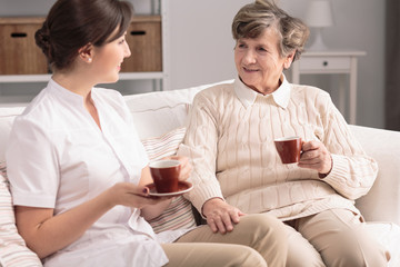 Friendly caregiver and smiling elderly woman drinking tea during meeting