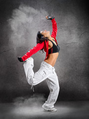 Young beautiful athletic woman jumping dancing modern style dance hip-hop on studio on wall background with smoke