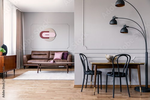 Real Photo Of Metal Lamp Standing Next To Dining Table With Two Black Chairs In Open