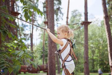 Child girl moves carefully along rope way.