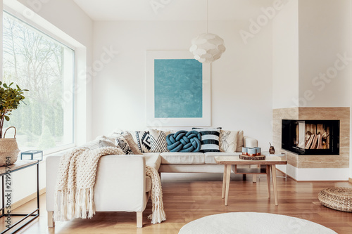 Turquoise Blue Knot Pillow On A Beige Corner Sofa And An Abstract Poster White