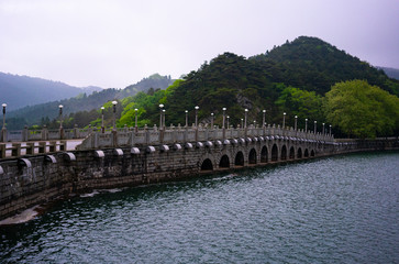 Chinese bridge over a dam with Lulin lake and green mountains view in Lushan National Park in China