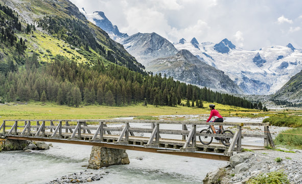 active senior woman, riding her e-mountain bike in the Roseg valley below the glaciers and summits of the Sella Group and Piz Roseg