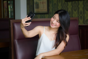 Portrait of thai china adult beautiful girl White shirt blue jeans using her smart phone