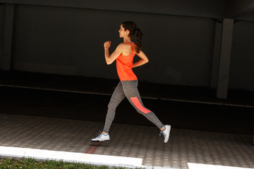 Female runner jogging trough parking lot.Fitness and jogging concept.