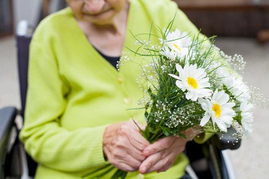 Elderly woman receiving flowers