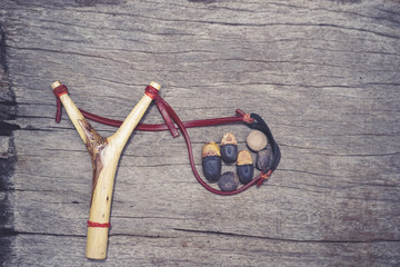 Sling shot. A wooden sling shot on wood. Processed in old film filter, vintage style.