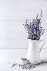 Pitcher with beautiful lavender flowers on white wooden table